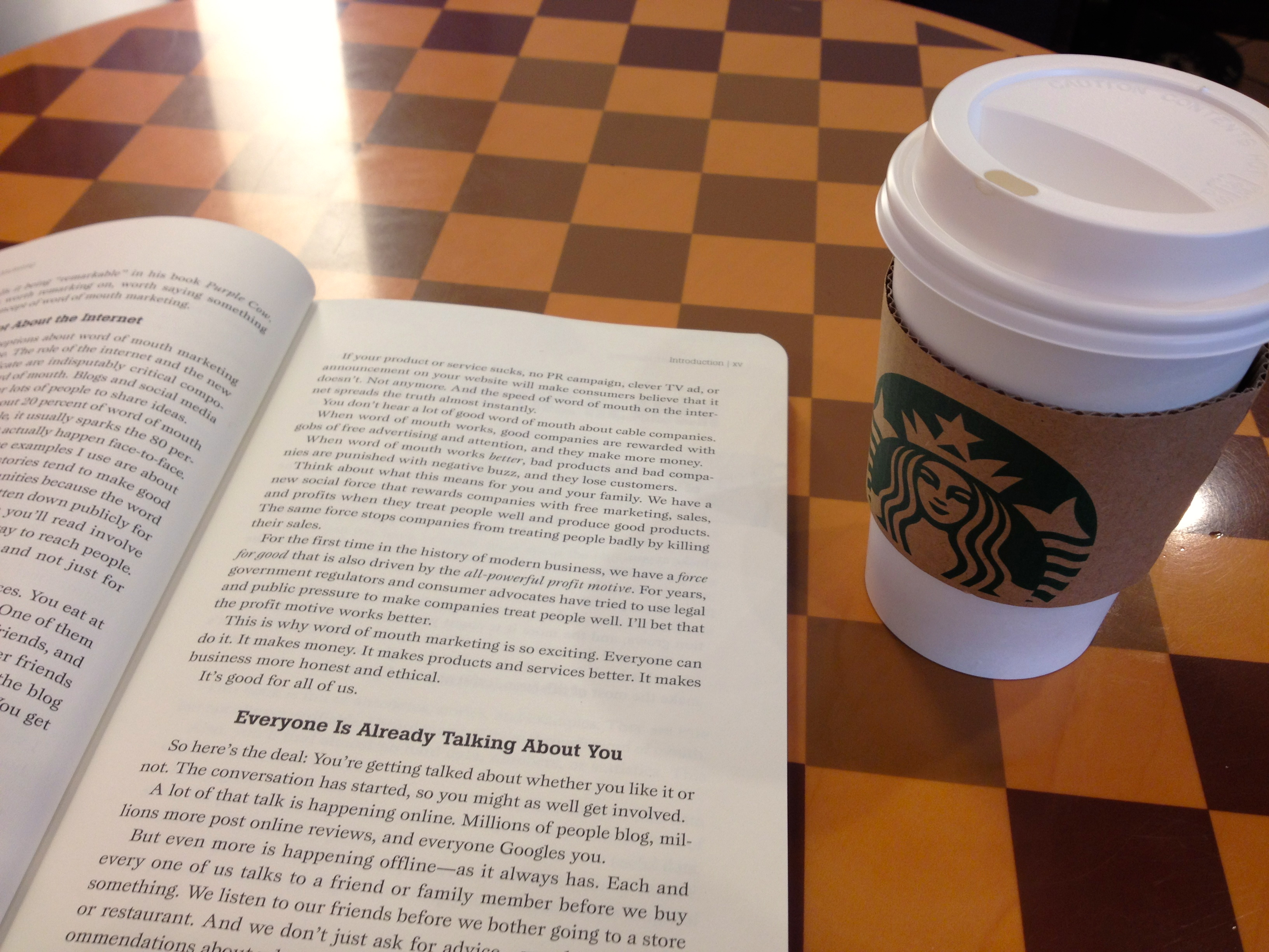 "at Starbucks with a book ""Word of Mouth Marketing"""